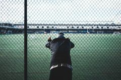 Tired young sporty man leaned and holding on to the rabitz fence. Runner resting near the fence. Concept stock images