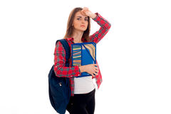Tired young students girl with backpack and folders for notebooks in her hands looking at the camera isolated on white Royalty Free Stock Photos