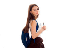 Tired young students girl with blue backpack on shoulder and folders for notebooks in hands looking at the camera Stock Images