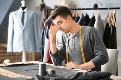 Tired young tailor. In atelier Royalty Free Stock Image