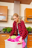 Tired young woman carrying laundry basket in kitchen Royalty Free Stock Photography