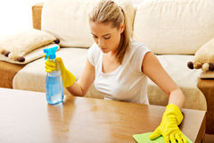 Tired young woman cleaning table in yellow gloves Royalty Free Stock Images