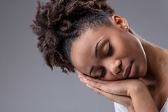 Tired young woman dozing with head on hands. Tired young woman dozing with her head resting on hands, closed eyes and a serene expression in a close up cropped royalty free stock photo