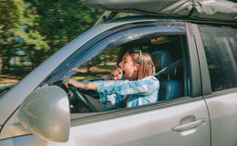 Tired young woman driving car and yawning Royalty Free Stock Photography
