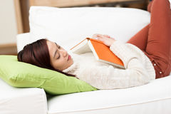 Tired young woman fallen asleep while reading Royalty Free Stock Image