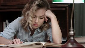 Tired young woman falling asleep over a book while sitting at the table after long day of work. Closeup shot. Professional shot on BMCC RAW with high dynamic royalty free stock image