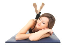 Tired young woman fitness lying on the blue mat Stock Photos