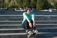 Tired young woman in funny sunglasses sits on the steps in the p Royalty Free Stock Photo