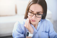 Tired young woman having toothache. Something with my teeth. Pretty young woman touching jowl and having toothache while sitting by the table royalty free stock image