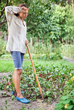 Tired young woman with hoe working in the garden Royalty Free Stock Image