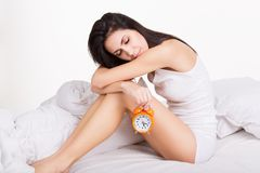 Tired young woman holding alarm clock. White Royalty Free Stock Images