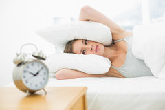 Tired young woman lying in her bed covering her ears with pillow Royalty Free Stock Photography