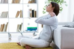 Tired young woman with neck pain using her laptop at home. Stock Photo