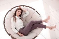 Tired young woman relaxes in a soft round chair. The concept of comfort royalty free stock images