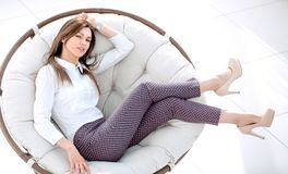 Tired young woman resting in a soft round chair. The concept of comfort stock images