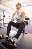 Tired young woman sitting in gym Stock Image