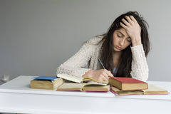 Tired  young woman sitting at her desk with books in front Stock Photo