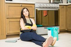 Tired young woman sitting on kitchen floor. Tired young woman with apron and protective latex gloves sitting on kitchen floor and resting of wiping tiles and Stock Photo