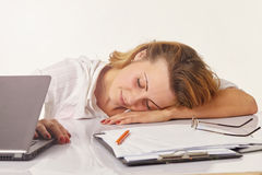 Tired young woman sleeping on des Royalty Free Stock Image