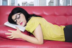Tired young woman sleeping on sofa with book Stock Photo