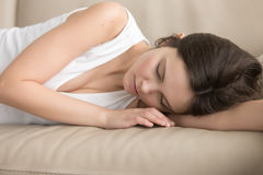 Tired young woman sleeping on soft sofa. Tired young woman in casual clothing sleeping on leather soft sofa. Lady resting after hard day, fell asleep exhausted Royalty Free Stock Photos