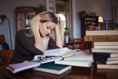 Tired young woman student of the University. Preparing exam and learning lessons in public library. royalty free stock photography