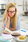 Tired young woman studying in kitchen Royalty Free Stock Image