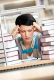 Tired young woman surrounded with books. Tired young woman with headache sitting at the desk surrounded with piles of books Royalty Free Stock Image