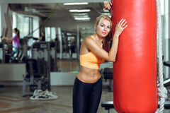 Tired young woman training with punching bag after training at gym Royalty Free Stock Photography