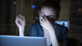 Tired young woman working on computer stock photos