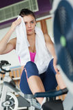 Tired young woman working out on row machine Royalty Free Stock Photos