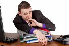 Tiredness. Young businessman yawning at his desktop - isolated stock photos