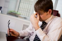 Tiredness. Photo of fatigue man with his eyeglasses off keeping his hand near face after hard working day Stock Photo
