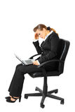 Tiredness business woman using laptop. Tiredness modern business woman sitting on chair and using laptop isolated on white stock photography