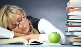 Tiredness student in library. Tiredness girl student sleeps on books in the library stock image