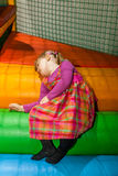 Tiredness. Tired little girl resting or sleeping on the colorful stairs in an indoor playground in an activity centre royalty free stock photography