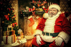 Tiredness. Tired Santa Claus sitting by the fireplace with a bag of gifts. Christmas home decoration stock photography
