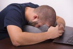 Tiredyoung IT经理谎言在枕头面对下来 死亡的概念从劳累过度的 免版税库存照片