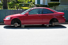 Tireless. A parked automobile on blocks whose wheels and tires have been stolen Stock Photos