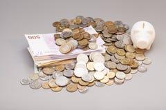 Tirelire avec des billets de banque et des pièces de monnaie Photos libres de droits