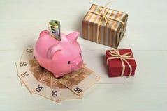 Tirelire avec des euros et des présents Photographie stock libre de droits