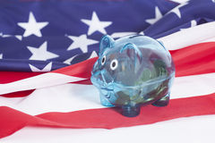 Tirelire avec des pièces de monnaie sur le drapeau national américain Photographie stock libre de droits