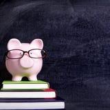 Tirelire avec des verres et le concept d'honoraires d'économie d'éducation de tableau noir Photographie stock
