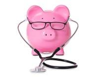 Tirelire avec le stéthoscope et les lunettes photos libres de droits