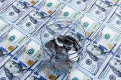 Tirelire avec les pièces en argent sur le fond américain des dollars Image libre de droits