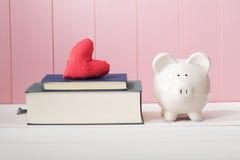 Tirelire blanche près des livres avec le coussin rouge de coeur Images stock