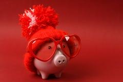 Tirelire dans l'amour avec les lunettes de soleil rouges de coeur avec le chapeau rouge et le pom-pom se tenant sur le fond rouge Photos libres de droits