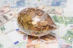 Tirelire en verre au-dessus d'euro et de dollars Image libre de droits