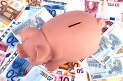 Tirelire entourée par d'euro notes Photo libre de droits