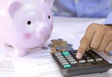 Tirelire et un homme d'affaires utilisant une calculatrice, pile de pièces de monnaie Photographie stock